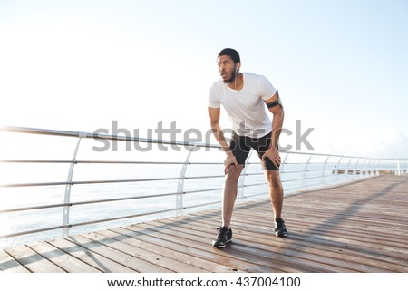 Focused african american young sportsman is ready to start running on pier - stock photo