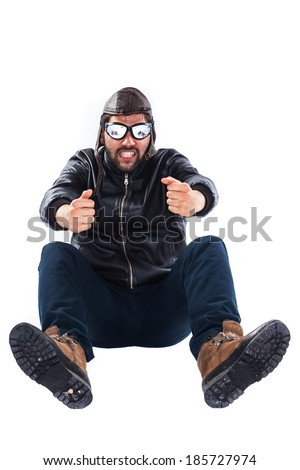 Focused and funny young bearded man dressed as a pilot is pretending to drive a racing car while holding his hands on an imaginary wheel  - stock photo