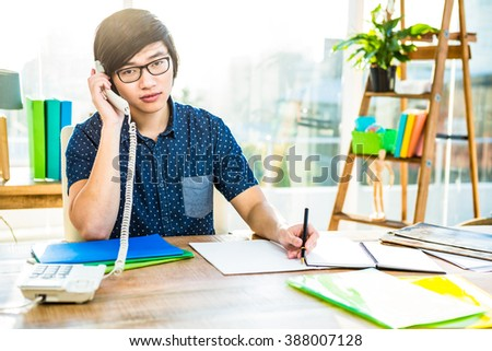 Focused asian businessman phone calling in office - stock photo