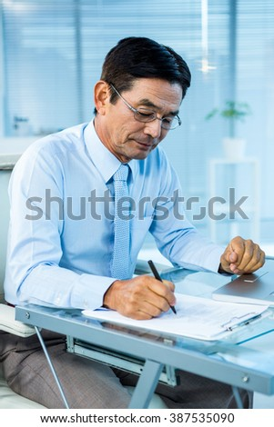 Focused asian businessman writing in office