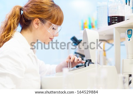 Focused attractive young life science professional measuring the absorbance of the solution in cuvette in the spectrophotometer. Focus on the researcher's face. - stock photo