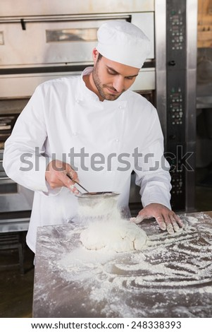 Focused baker sieving flour on the dough in the kitchen of the bakery