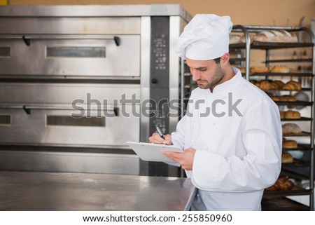 Focused baker writing on clipboard in the kitchen of the bakery - stock photo