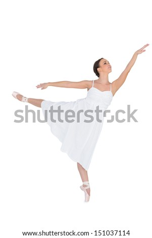 Focused ballet dancer posing on her tiptoe while rising a leg on white background  - stock photo