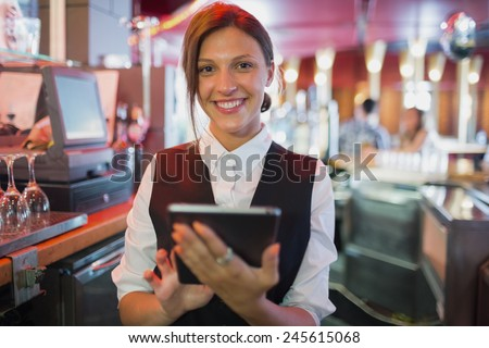 Focused barmaid using touchscreen till in a bar - stock photo