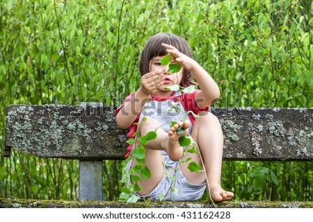 focused beautiful small boy playing with hands and legs with foliage and long stems of ivy to learn nature sitting on a mossy bench in garden in summertime