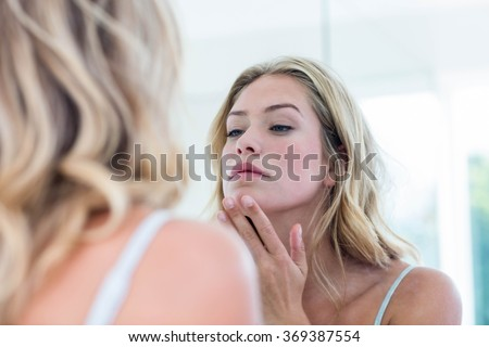 Focused beautiful young woman looking at herself in the bathroom mirror at home - stock photo