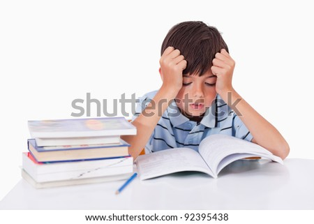 Focused boy learning his lessons against a white background - stock photo