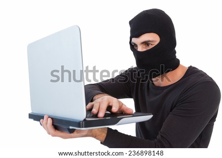 Focused burglar with balaclava holding laptop on white background