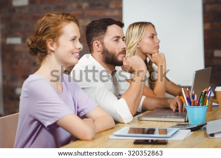 Focused business people with technologies sitting in creative office