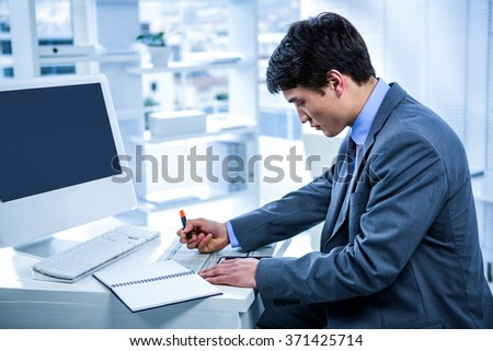 Focused businessman highlighting a document in his office - stock photo