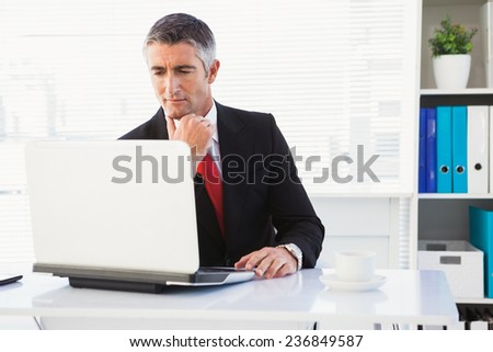 Focused businessman in suit using his laptop in his office