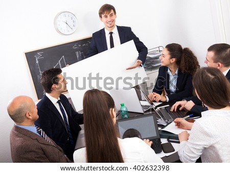 Focused businessman presents new development plan at poster in the office - stock photo