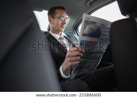 Focused businessman reading the newspaper in his car - stock photo