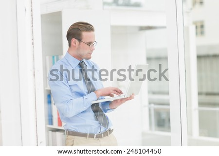 Focused businessman standing and using laptop in his office