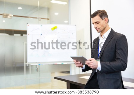 Focused businessman standing and using tablet in office - stock photo