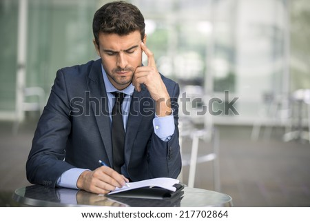 Focused businessman thinking and writing outside office into report file calculating stock market earnings  - stock photo