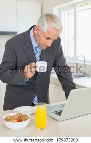 Focused businessman using laptop in the morning before work at home in the kitchen