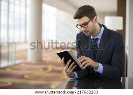 Focused businessman with glasses using smart electronic tablet at the hotel airport lobby checking stock market report - stock photo