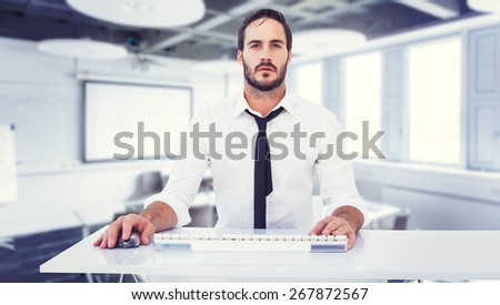 Focused businessman working on computer against classroom