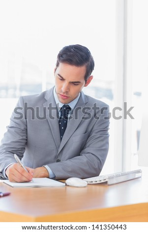 Focused businessman writing at his desk in the office