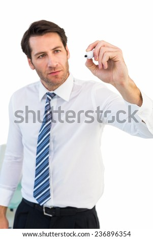 Focused businessman writing with marker on white background