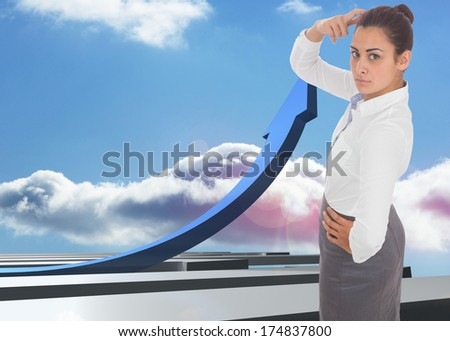 Focused businesswoman against blue curved arrow pointing up against sky
