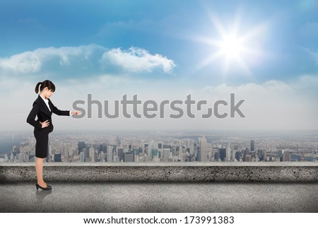 Focused businesswoman pointing against balcony overlooking city