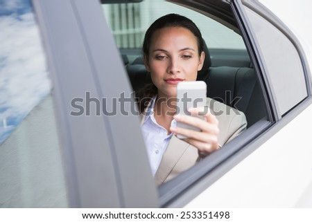 Focused businesswoman using her phone in her car - stock photo