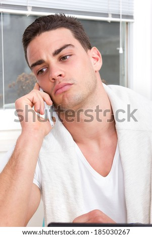 focused casual handsome man talking on mobile phone in the living room atmosphere