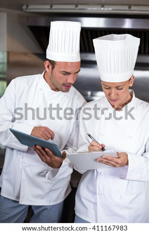 Focused chefs holding clipboards in commercial kitchen