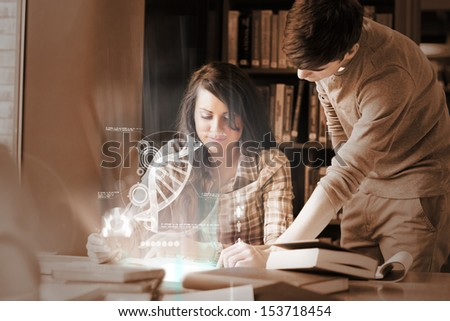 Focused college students analysing dna on digital interface in university library - stock photo