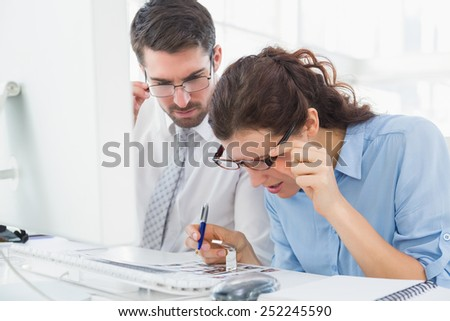 Focused coworkers looking photos together in the office - stock photo