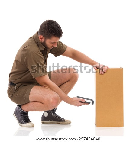 Focused delivery man crouching close to carton box and using scanner. Full length studio shot isolated on white. - stock photo