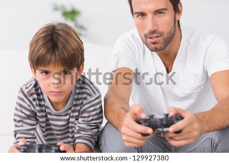 Focused father and son playing video games together on the couch
