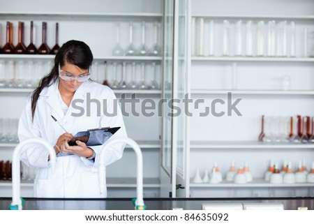 Focused female scientist writing on a clipboard in a laboratory - stock photo