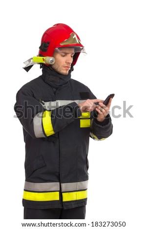 Focused fireman using smart phone. Three quarter length studio shot isolated on white. - stock photo