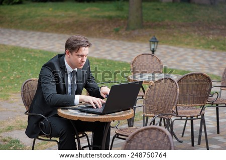 Focused freelancer. Attractive young caucasian businessman in formal wear working on laptop while sitting at the table outdoors. - stock photo