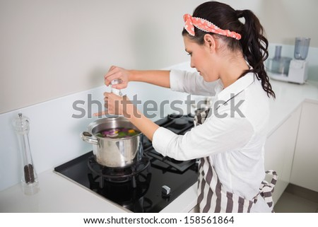 Focused gorgeous cook putting salt on vegetables while cooking in bright kitchen - stock photo