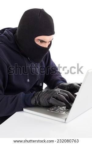 Focused hacker in balaclava hacking laptop on white background