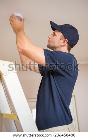 Focused handyman installing smoke detector with screwdriver on the ceiling - stock photo