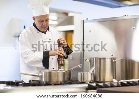 Focused head chef flavoring food with pepper in professional kitchen