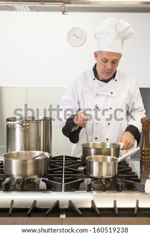 Focused head chef looking into pot in professional kitchen - stock photo
