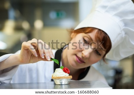 Focused head chef putting mint leaf on little cake in professional kitchen - stock photo