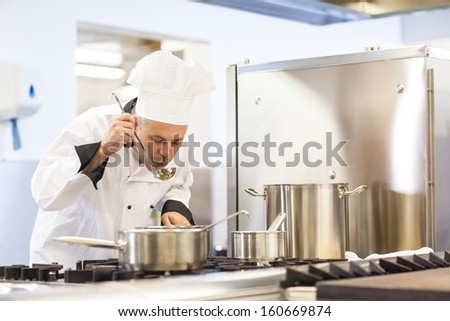 Focused head chef tasting food from ladle in professional kitchen - stock photo