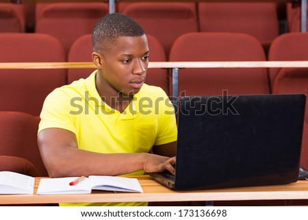 focused male african university student using laptop  - stock photo