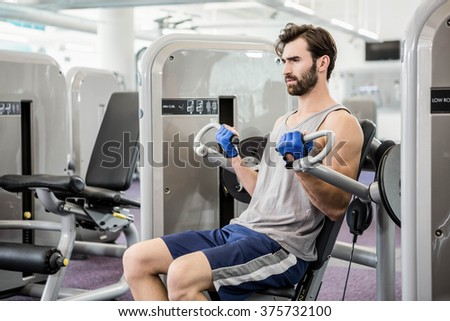 Focused man using weights machine for arms at the gym - stock photo