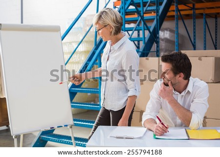 Focused manager taking notes during presentation in a large warehouse
