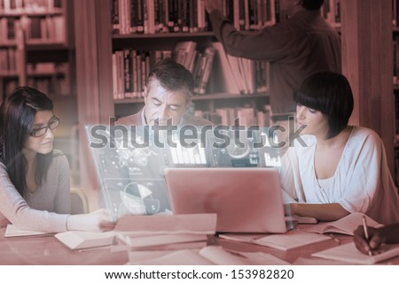 Focused mature students working together on digital interface in university library - stock photo