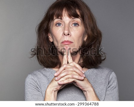 focused mature woman with brown hair and grey sweater thinking,playing with her fingers,looking straight sad and angry - stock photo